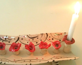 A menorah for hanukkah made of clay .