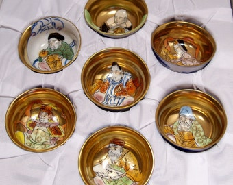 Set of Seven Asian Oriental Sake Cups Hand Painted Gold Figures Inside Blue and White Porcelain Outside