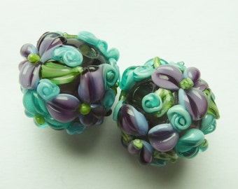 Glass lampwork beadset with raised flowers.