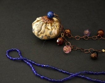 Long necklace with blue et god coloured fabric, glass beads and chain