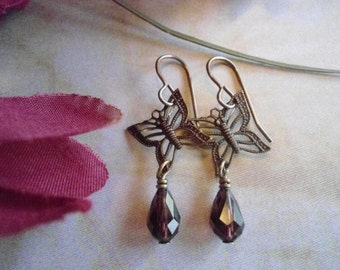 Amethyst butterfly earrings:  Vintaj brand asymmetrical antique brass butterfly earrings made with burgundy czech teardrop crystals!