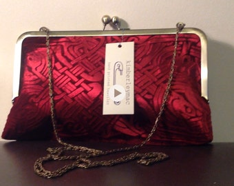 A Crimson kisslock clutch bag in an embossed iridescent velvet celtic design