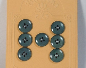 7 Buttons in mother of pearl turquoise 18 mm 4 holes.