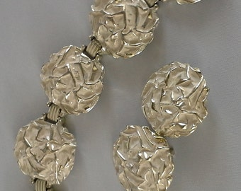 Vintage 1961 Sarah Coventry matching set bracelet and clip on earrings, made of  silver tone and white enamel