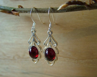 Ruby red Swarovski crystal leaf drop earrings. Silver plated leaf design with ruby red crystal. Ruby is the birthstone for July.