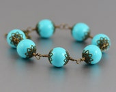 Bracelet Featuring Turquoise Glass Antiqued Brass Filigree Caps Flower Detail Toggle Clasp