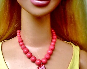 Barbie wearing an orange to salmon jewelry set with a deep orange and white pendant.