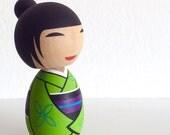 Kokeshi doll. Kimono girl in Green