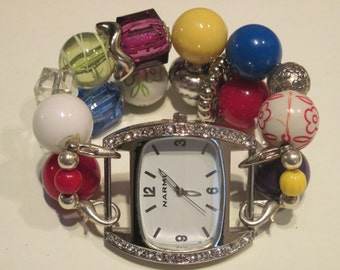 Multi colored and silver plated acrylic beaded watch band. Includes white watch face
