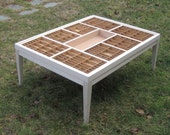 Large coffee table with a removable glass top and various sized compartments made of repurposed letterpress boxes. A unique display table.