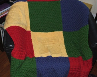 Hand knit blanket in beautiful primary colors and 100 % machine washable Acrylic