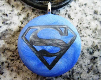Super Hero hand carved on a polymer clay blue pearl color background. Pendant comes with a FREE 3mm necklace