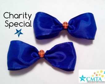 CMTA pair of blue hair bows with orange howlite skulls. 50% of sale goes to charity.