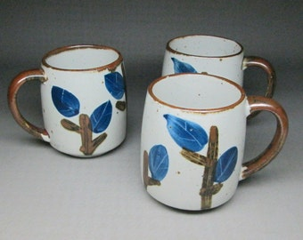 set of three otagiri mugs , colors similar to the horizon line . a little branch with leaves . blue & brown
