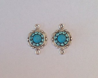 1 pair of Swarovski crystal connectors, with Turquoise and Light Turquoise stones. Antique silver colour.