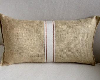 blonde burlap lumbar pillow with decorative tape in orange
