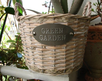 shabby chic,woven wicker planter or storage baske with plastic lining & handles.