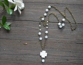 Long light blue and neutral small beads on a gold brass chain with a creamy white jade cross pendant