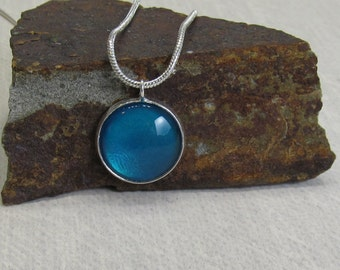 Teal glass cabochon on shiny silver necklace