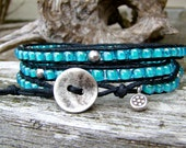 Wrap bracelet with blue aqua lined japanese seed and round pewter beads on a black waxed cotton cord