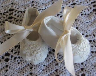 Off white satin baby shoes with lace trim.