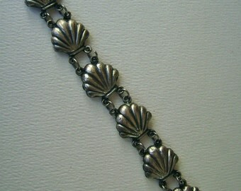 silver scallop shells in a row:  a bracelet