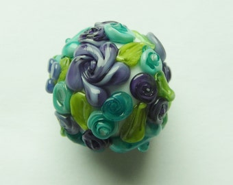 Focal glass lampwork bead in white with raised flowers.