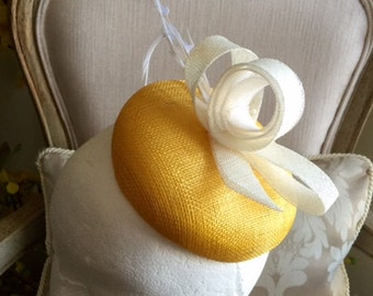 Stunning yellow round base fascinator with white sinamay loops and feathers