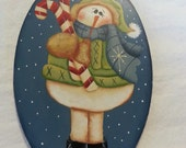 Snowman on ice skakes oval with a cardial birdhouse candle