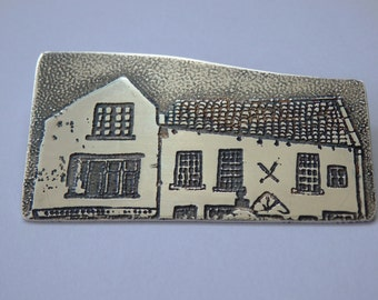 Silver brooch , etched with houses