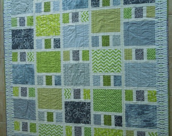 Modern patchwork quilt made with cotton fabrics in shades of green and grey with an ivory background and quilted on a domestic machine