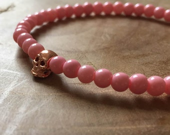 Pink and Rosé Skull: an elastic beaded bracelet with rosegoldtone skull and soft pink glass beads.