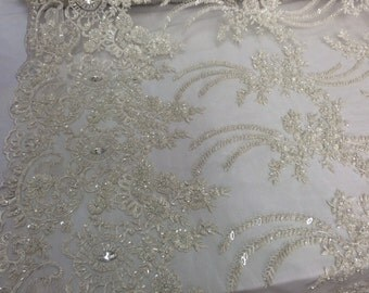 Ivory french design embroidered and heavy beaded on a mesh lace.36x50inches. Wedding-Bridal fabric lace. Sold by the yard.