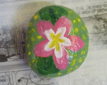 Small handpainted rock with green, yellow, and pink flower