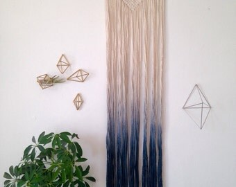 Macrame wall hanging, dip dyed ombre in bluish grey, cotton on a wood dowel. Geometric triangle shape.