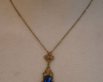B12) A lovely vintage gold tone metal ornate Edwardian style pendant necklace with blue faceted glass and chain