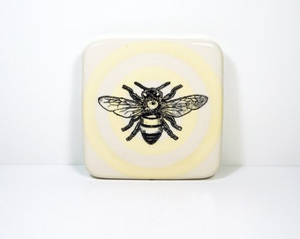 tile with a honey bee on a buttercream bullseye, made to order.
