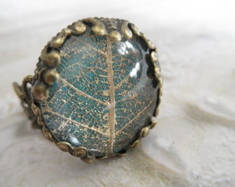 Gold Skeleton Leaf Victorian Bronze Filigree Ring Atop Glowing Blue-Green Background,Symbolizes Tranquility, Serenity-Gifts Under 20 Dollars