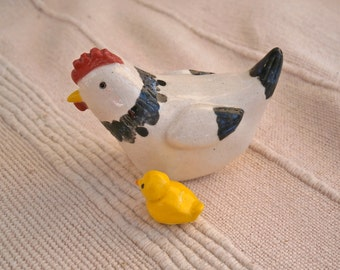 Black and white hen figurine with yellow chick, miniature ceramic chicken, small hen sculpture