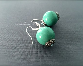 Mint Green Round Ceramic Earrings. Large Ball Statement Earrings. Silver Floral Bead Caps. Green Blue. Under 15 Gifts. Silver.