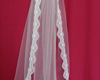 Lace edged single tier elbow length white wedding veil. Lace bridal veil