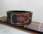 Guitar: Acoustic Guitar on Leather Bracelet.