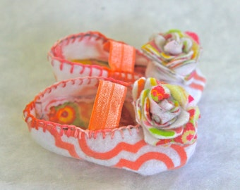 Baby booties that celebrate a precious life. The booties are handmade out of soft felt, and the decorative detailings are all done by hand.
