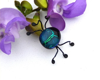 Fused dichroic glass bug in muted green with a bright shiny stripe