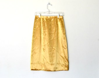 Vintage 40s gold satin skirt Zip and clasp back closure Hemmed by hand Distinctive waistband / size medium