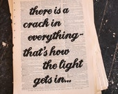 "Art Print: ""There is a crack in everything, that's how the light gets in."" – Leonard Cohen quotation on (broken dictionary) book page"
