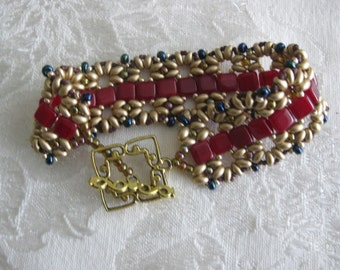Down the Garden Path Beaded bracelet in dark red and gold.  Many teams use these colors