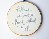 Hoop art / A house is not a home without a cat / quote / periwinkle hand embroidery / white background in 6 inch wood embroidery hoop