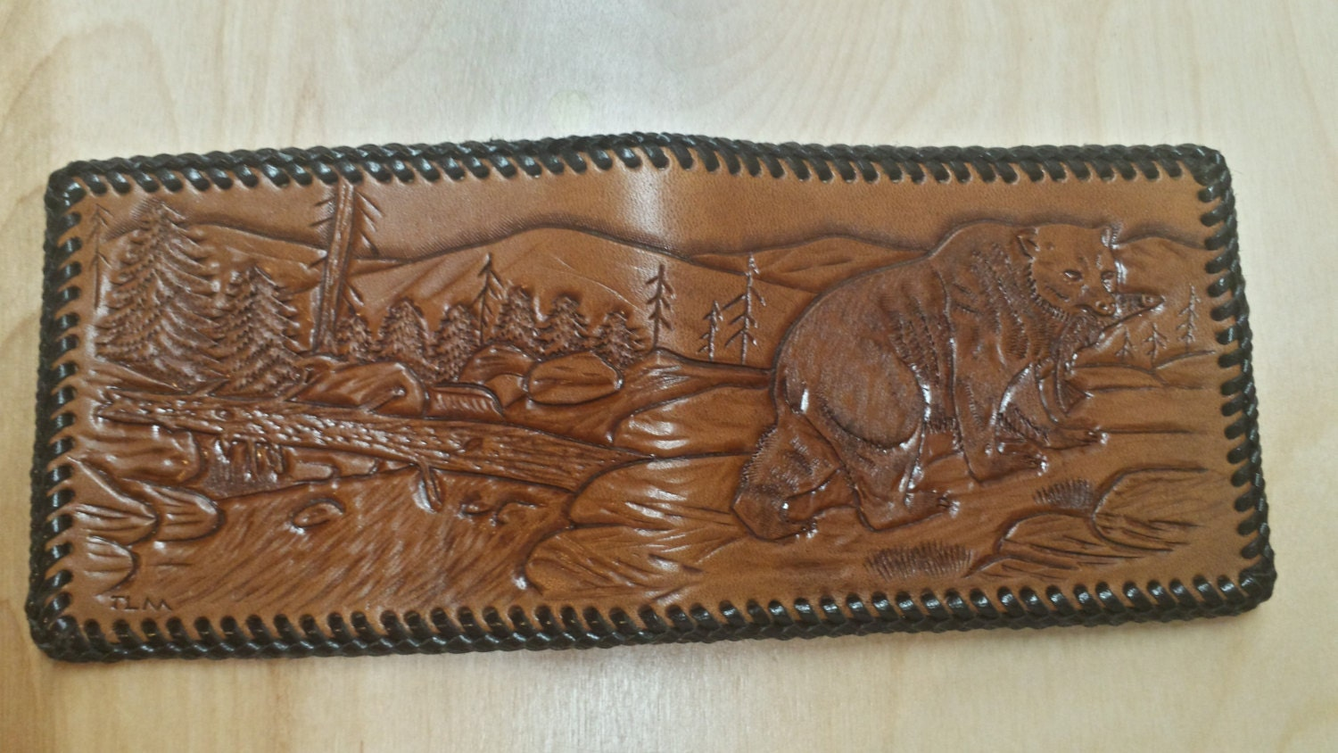Hand tooled leather wallet carved with a bear scene