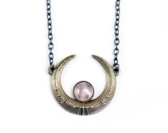 Eclipse necklace - A crescent Moon necklace inscribed with runes and focusing on a Rose Quartz gemstone.